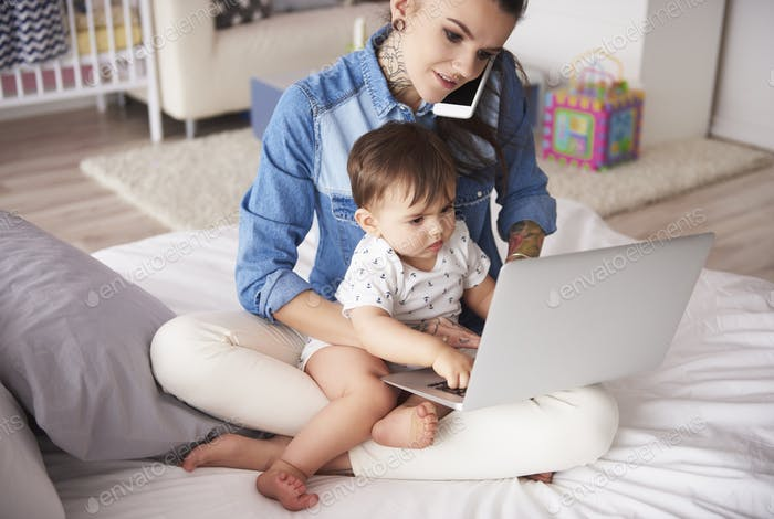 Young mother working from home with son