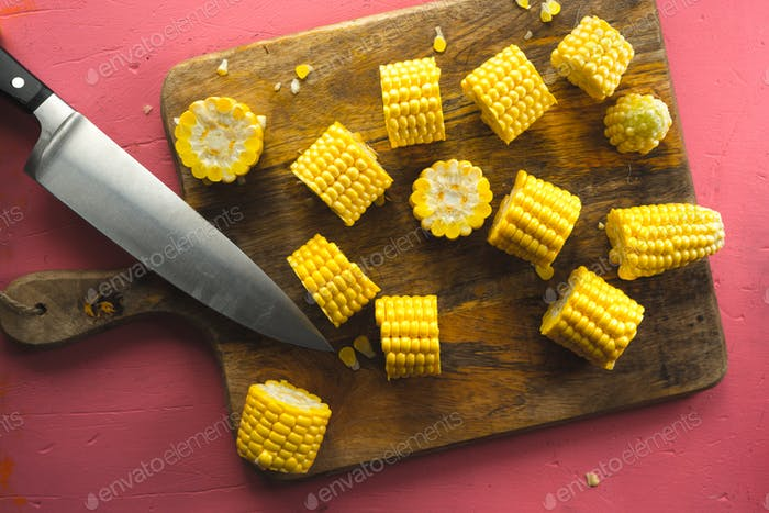 Large pieces of corn on a cutting board and kitchen knife