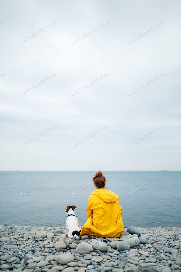 Frau mit Hund an der Küste