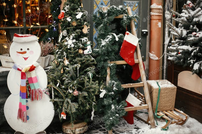 Stylish christmas tree with festive ornaments, snowman and ladder with stockings at store