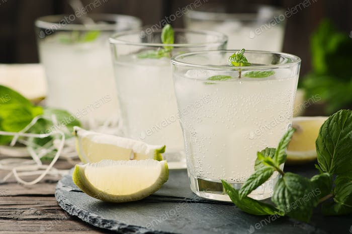 Fresh cocktail with lemon, ice and mint on the vintage table