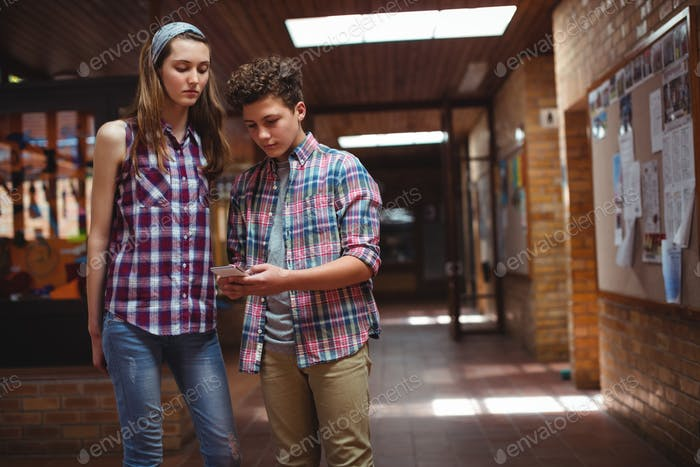 Classmates using mobile phone in corridor at school