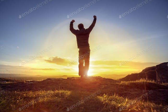Hombre Alegre celebrando el éxito ganador contra la puesta de sol