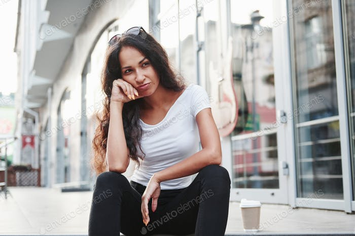 Feels bored. Beautiful woman with curly black hair have good time in the city at daytime