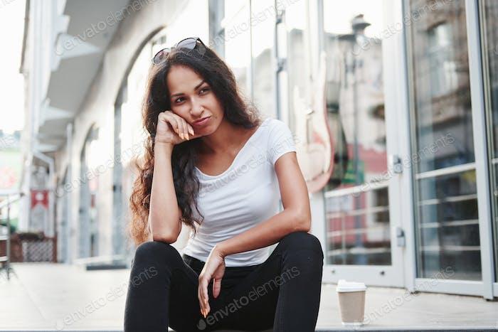 Fühlt sich gelangweilt an. Schöne Frau mit lockigen schwarzen Haaren haben gute Zeit in der Stadt am Tag