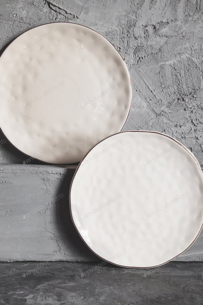 Gray empty plates (ceramic) on a gray stone background. Gray minimalism concept