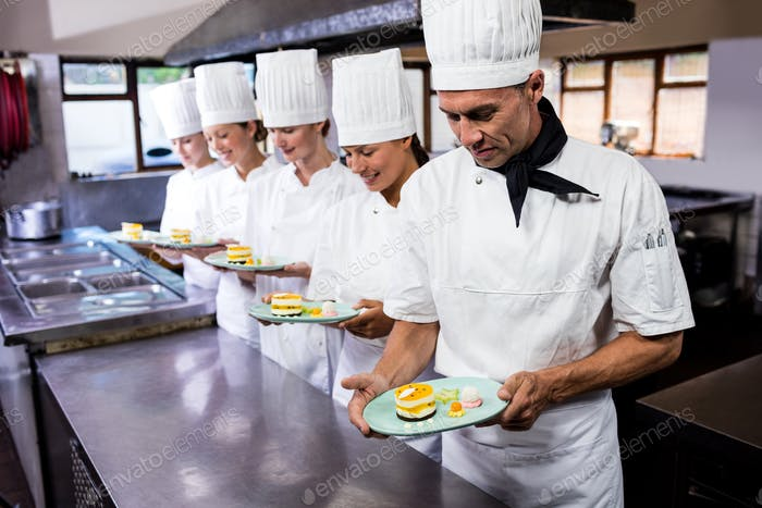 Group of chefs holding plate of delecious desserts in kitchen at hotel