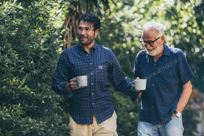 Father-son bonding. Cheerful young man drinking coffee together with him
