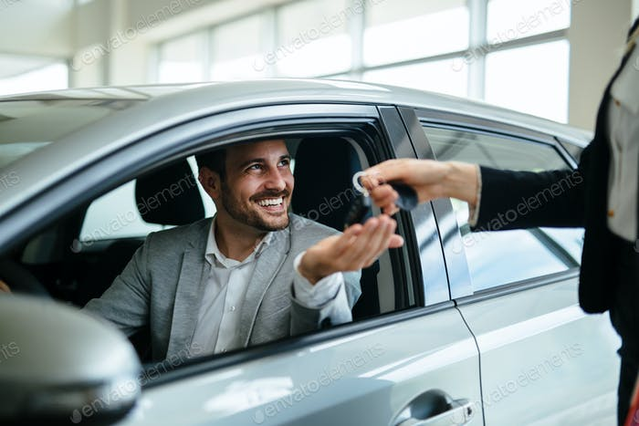 Professional salesperson during work with customer at car dealership. Giving keys to new car owner.
