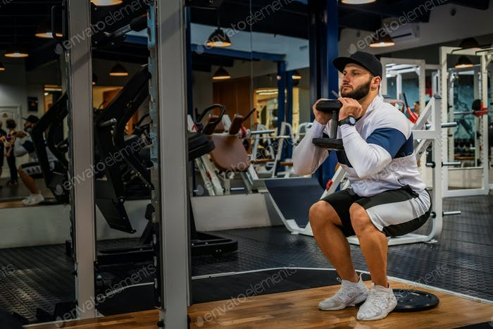 Young man does static or isometric squats in gym