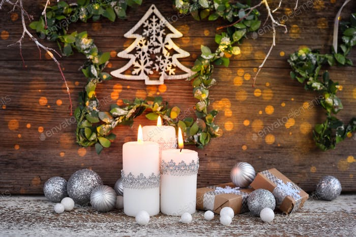 Christmas composition with candles and festive decorations on a wooden background