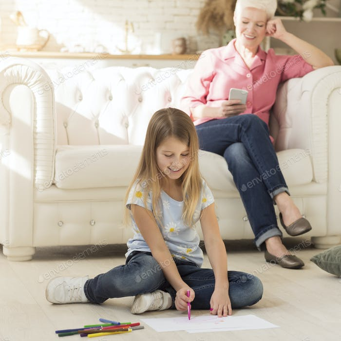 Little girl drawing on floor next to her granny