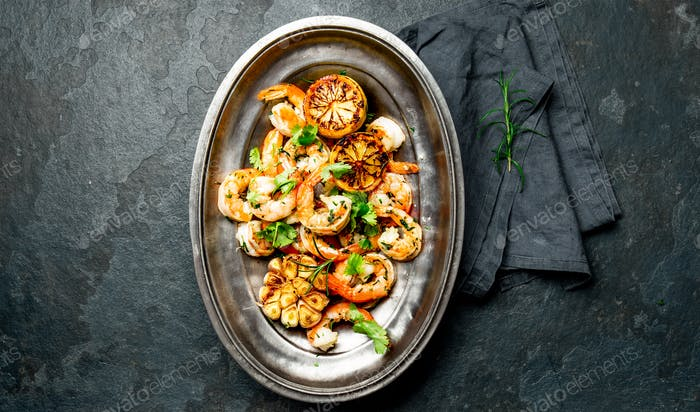 Grilled roasted shrimps prawns on oval metal vintage plate, top vie. Slate background.