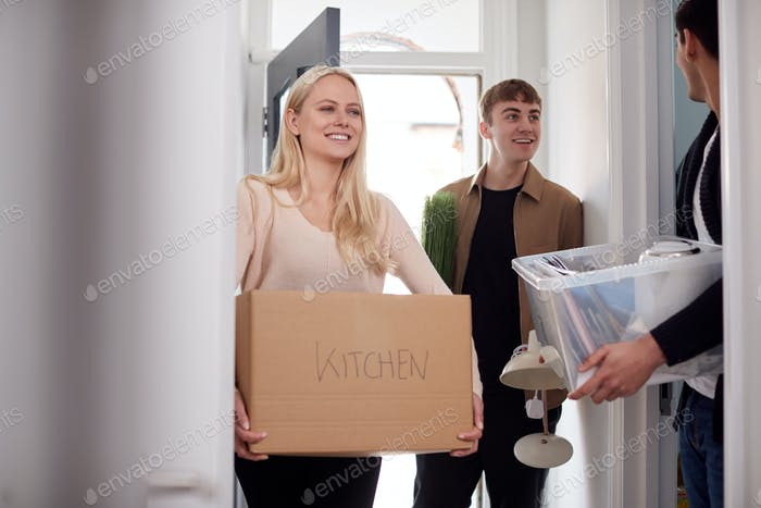 Group Of College Student Carrying Boxes Moving Into Accommodation Together