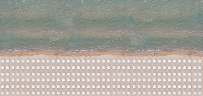 Aerial drone view of a sandy beach with umbrellas and deck chairs, a summer sunny day.