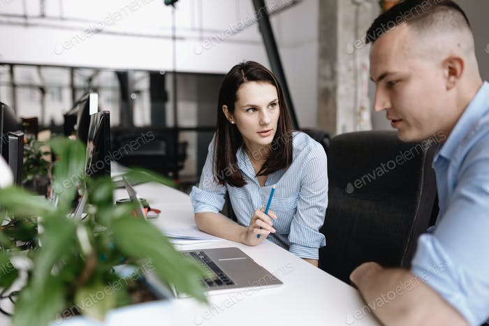 Beautiful woman and guy dressed in office style clothes are working together with laptop sitting at