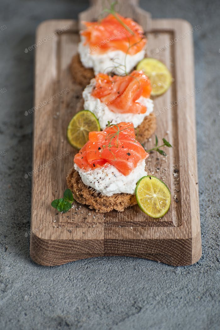 Miniature toasts with lightly salted salmon and cottage cheese c
