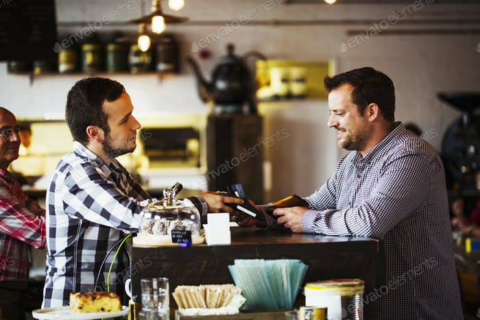Specialist coffee shop. Two men, a barista and a client talking over the coffee shop counter.