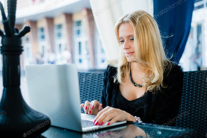 Beautiful serious young woman in casual clothes sitting in street cafe working on laptop