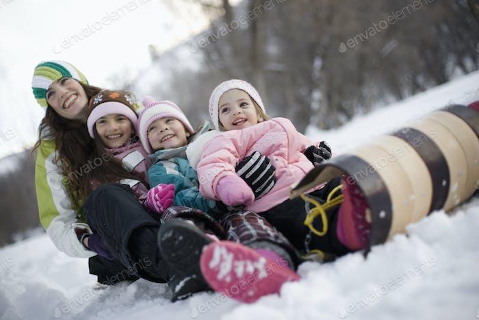drei Kinder und eine erwachsene Frau sitzt auf einem Schlitten im Schnee.