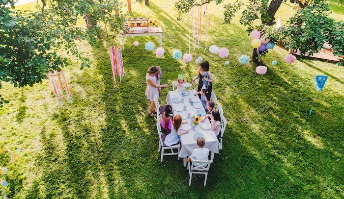 Hohe Ansicht von kleinen Kindern sitzen am Tisch draußen auf Gartenparty.