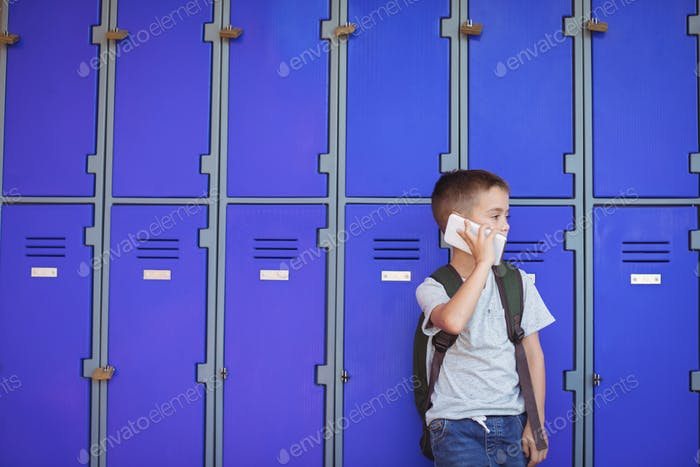 Elementary boy talking on mobile phone against lockers