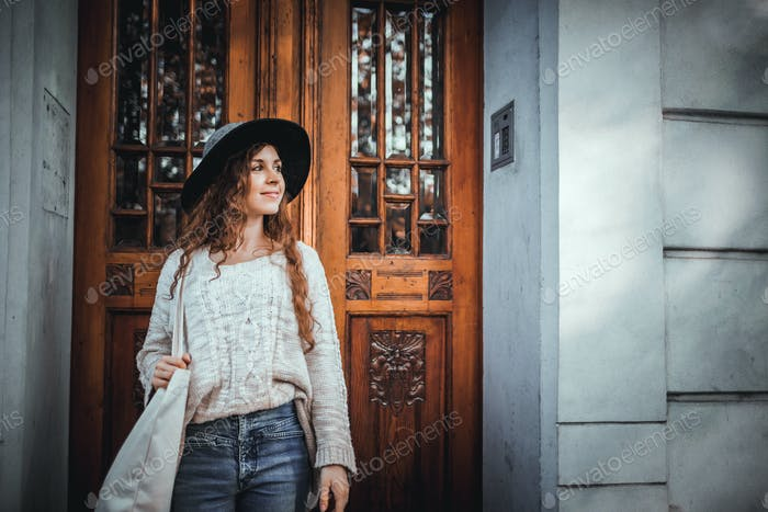 Young fashionable woman standing in old stylish door of building