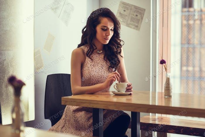 Frau sitzt in städtischen Café bewegen Teelöffel in Kaffeetasse