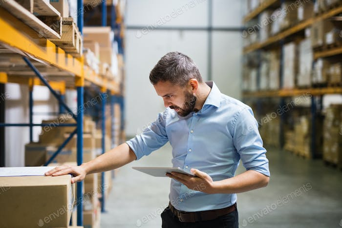 Man warehouse worker with a tablet.