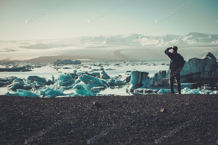 Man explorer lookig at Jokulsarlon lagoon, Iceland.