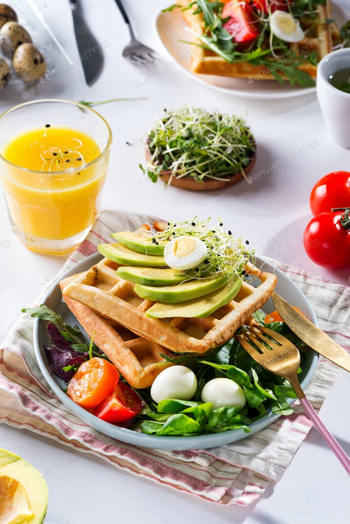 Breakfast time. Waffle with salad, egg, juice and avocados for breakfast. View from above