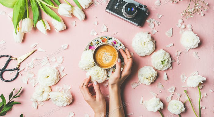 Female hands holding coffee, flowers and film camera, wide composition