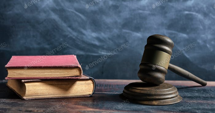 Judge gavel, old books and reading glasses on a wooden table, black board background.