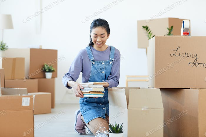 Young Asian Woman Unpacking Boxes