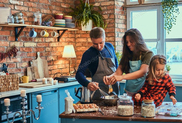 Adorable family together cooking breakfast in loft style kitchen.