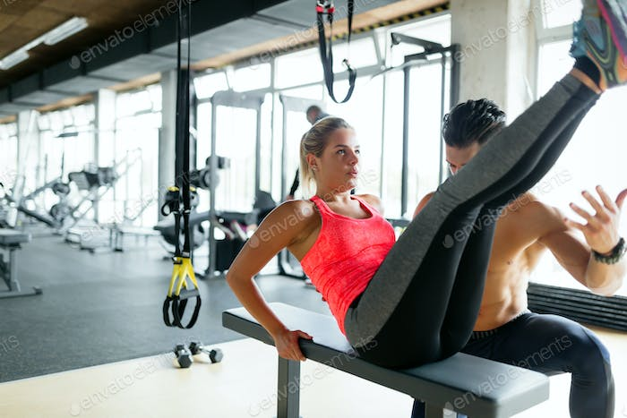Young beautiful woman working exercises with trainer