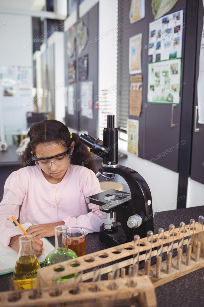 Concentrated elementary student writing in book by microscope at laboratory