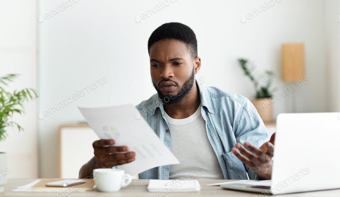 Concerned businessman checking financial reports of his company