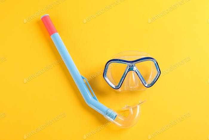 Snorkel and diving mask on yellow background, space for text