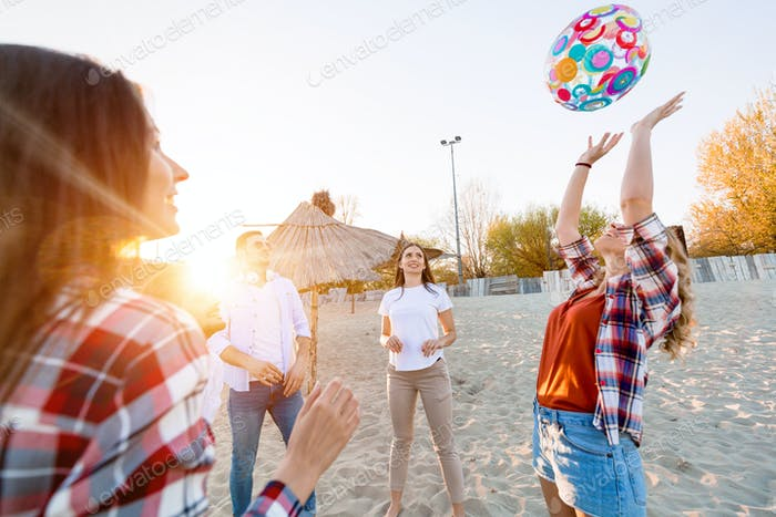 Group of happy friends partying on beach