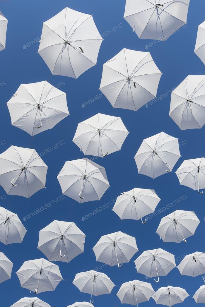 Weiße Regenschirme am blauen Himmel