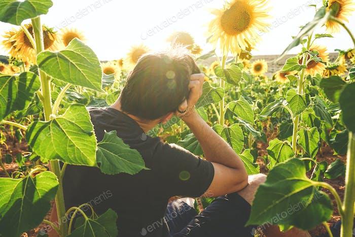 Junger Mann genießen den Tag in einem Feld von Sonnenblumen