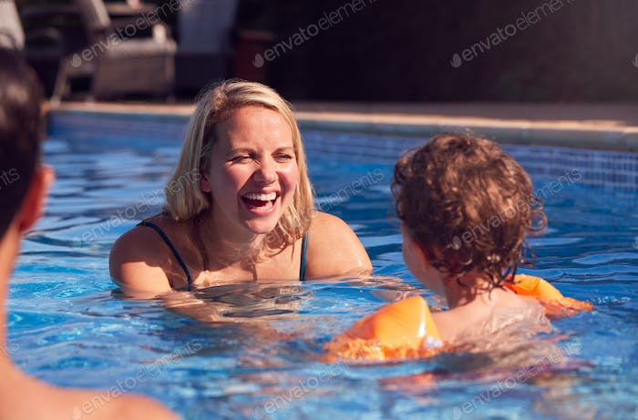Family In Outdoor Pool On Summer Vacation Teaching Son To Swim With Inflatable Armbands