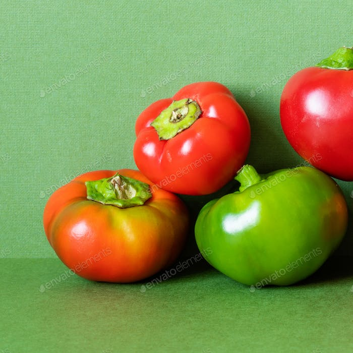 Bell peppers composition on a green background.