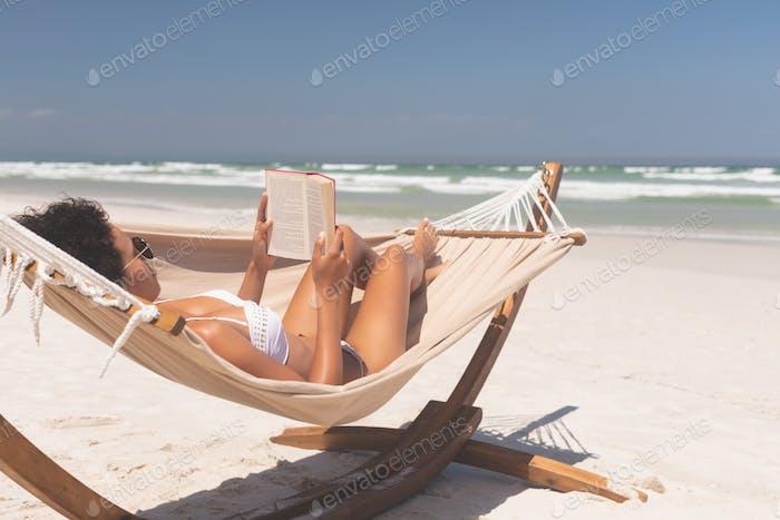 Beautiful woman in bikini reading on hammock while sun bathing at beach