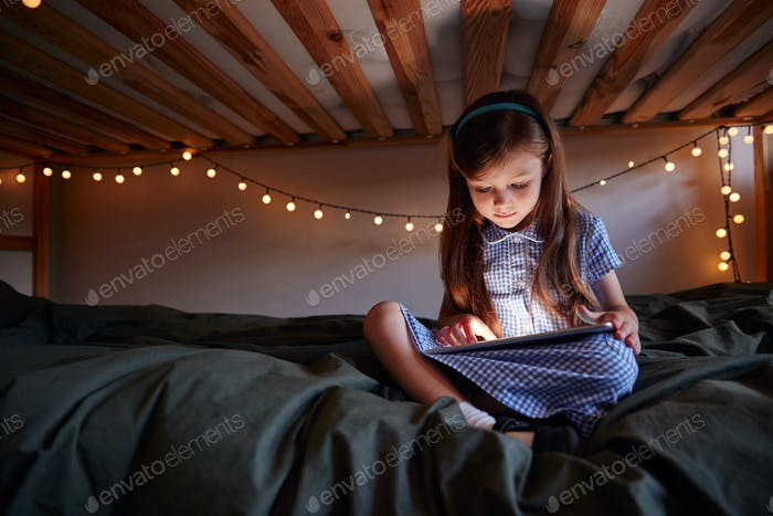 Young Girl Sitting On Bed At Home Decorated With Fairy Lights Using Digital Tablet