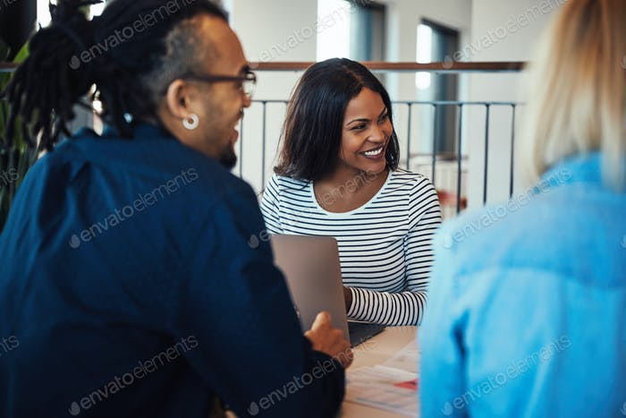 Young African American businesswoman laughing with office colleagues