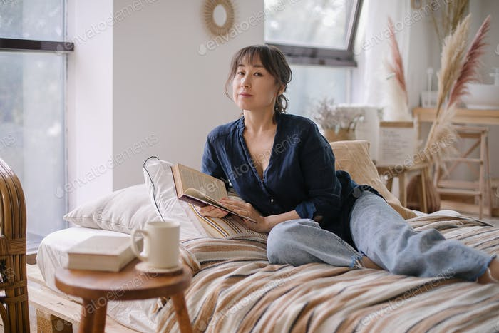 Beautiful young Asian woman reading a book. Enjoying a quiet time and relaxing at cozy home