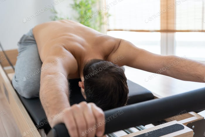 Man exercising on pilates reformer bed
