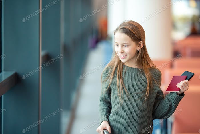 Adorable little girl at airport in big international airport near window